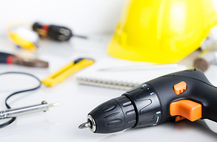 Repair man, construction worker tools on white background. Focus on screwdriver